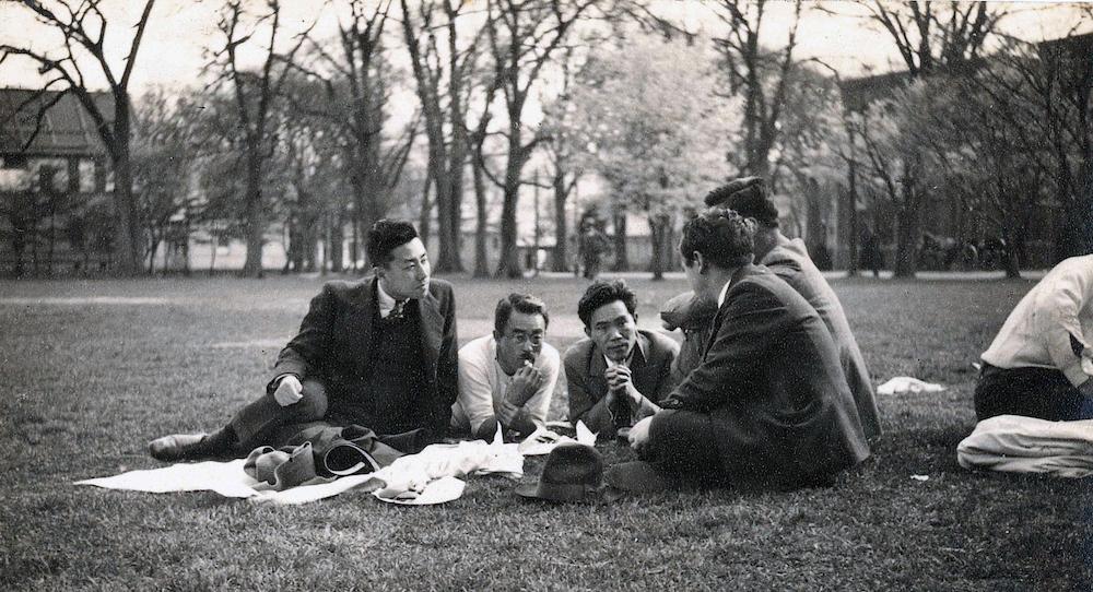 芝生の上でくつろぐ教官たち(左から2 人目が堀健夫,その右が中谷宇吉郎。右後方の建物は理学部 写真: 北海道大学大学文書館提供)